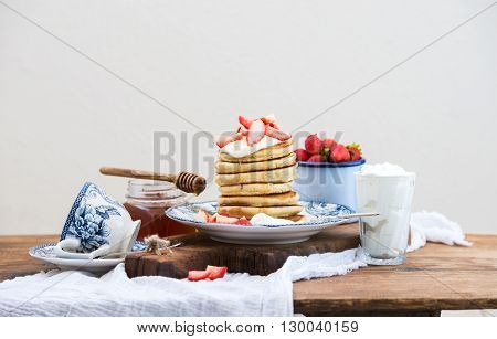 Breakfast set. Pancaks with fresh strawberries, sour cream and honey on a porcelain plate over rustic wooden table. Blue enamel cup full of berries behind, white background, selective focus