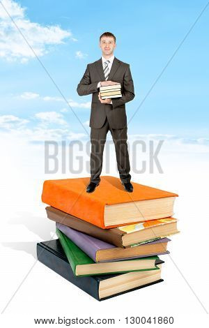 Man stand on pile of book and hold books. Blue sky and cloud at background