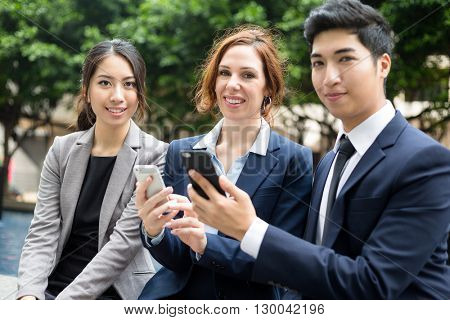 Business people using cellphone together