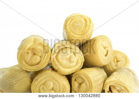 a pile of marinated artichoke hearts on a white background