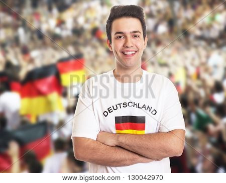 Handsome german fan with dark hair with other fans in the background