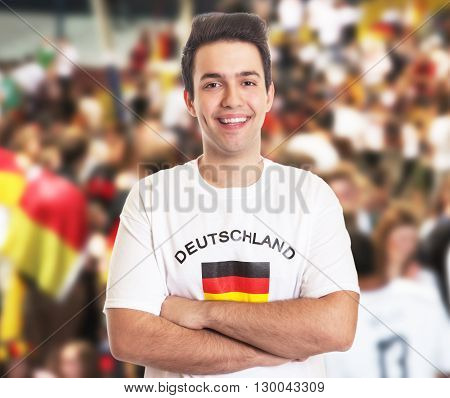 Attractive german fan with dark hair with other fans in the background