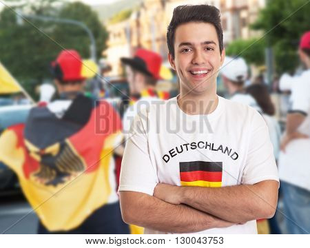 Cool german fan with dark hair with other fans in the background