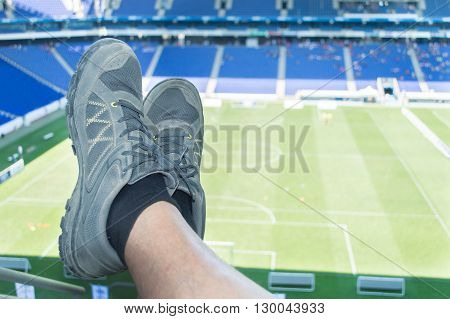 closeup of crossed legs of man resting at the seat of football stadium