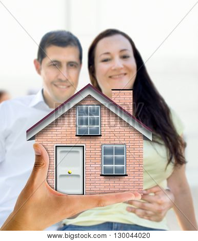A cropped view of a couple happy with miniature house offering you a real estate agent for your future home of your dreams couple
