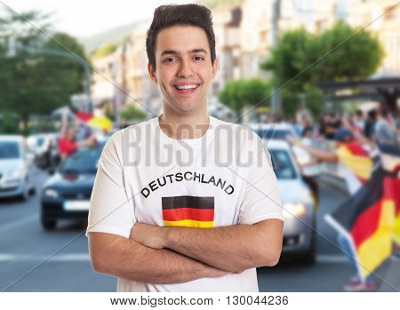 Happy german fan with dark hair with other fans in the background