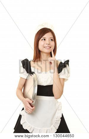 portrait of young Japanese woman wearing french maid costume thinks about something on white background