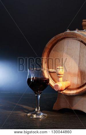 Nice oak barrel near wineglass with red wine on dark background