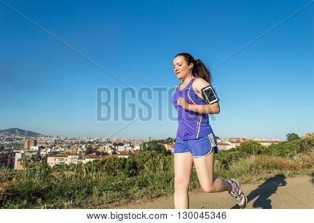 woman running at the city park listening to music on smartphone in summertime