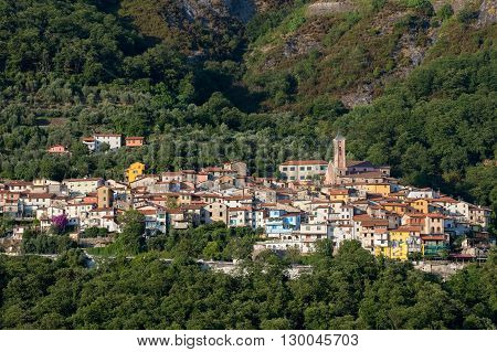 Small Mountain Village - nestled into the Italian Apuan Alps. The European village of Antona, a small Tuscan town with red tiled roofs and a pink church bell tower.