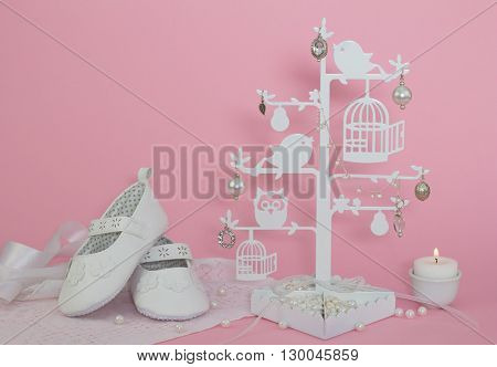 Baby girl shoes candle and pearls pink invitation background
