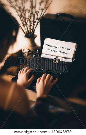 Gratitude is the sign of noble souls message on a white background against rear view of a woman is using a writing machine