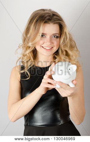 Happy Woman In Black Dress With A Piggybank.