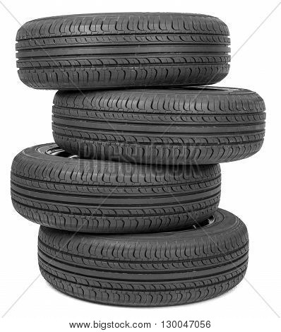 Stack of four wheel black tyres for summer isolated on white background