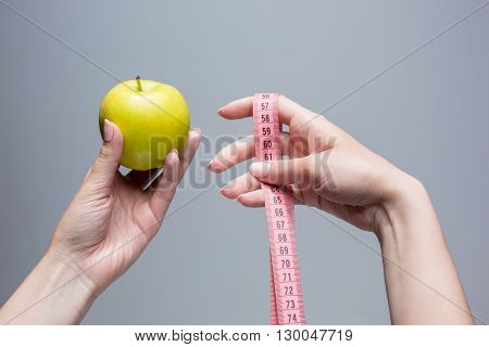 Green apple and tape in female hands on gray background. Weight loss, diet and detox concept