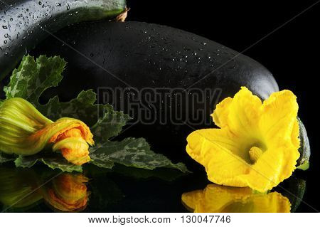 Wet Courgettes With Flowers On Black Background
