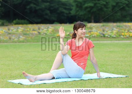 Japanese woman outside doing yoga Half Lord of the Fishes pose