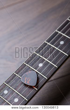 Guitar Frets With Strings And Mediator On Dark Brown Surface