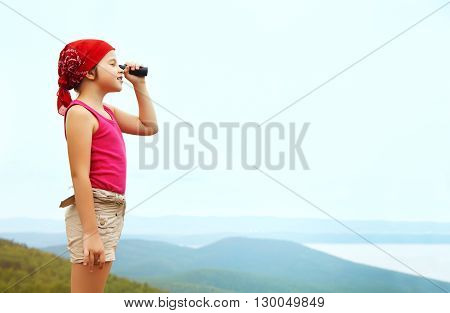 funny little girl in a bandana with a spyglass. children outdoors