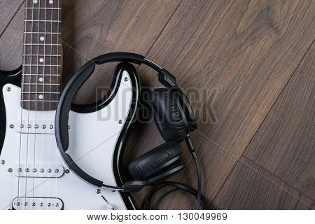 Electric Guitar With Headphones On A Brown Wooden Floor