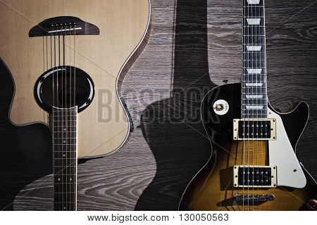 The electric and acoustic guitar on the wooden floor