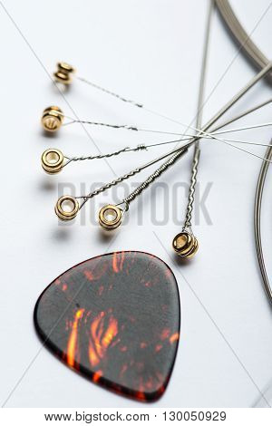 Electric Guitar Strings With Mediator On White Surface