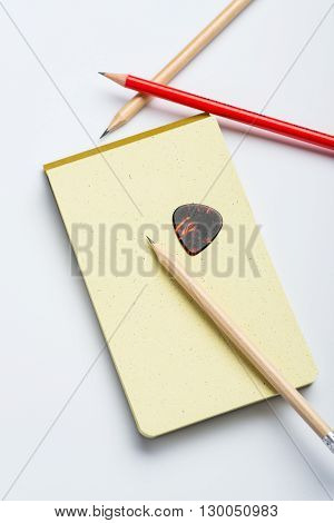Yellow Notepad With Two Pencils And Mediator On White Surface