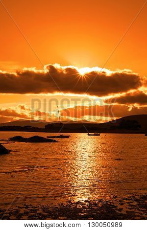boats in a quiet bay near kenmare on the wild atlantic way ireland with an orange sunset