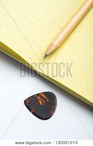 Yellow Notepad With Pencil And Mediator On White Surface