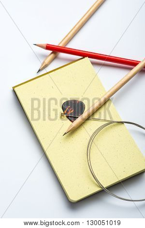 Yellow Notepad With Three Pencils, String And Mediator On White Surface