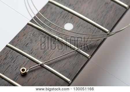 Electric guitar frets with new string on white