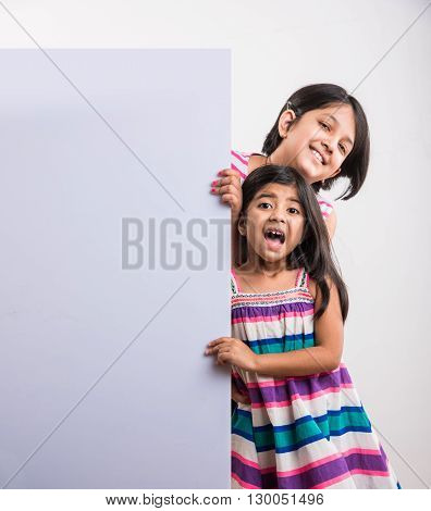 two cute Indian little girls presenting with a blank white board, little asian girls presenting white board with blank copy space