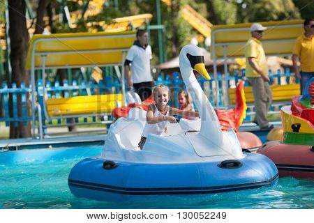 Child on water in the  boat - swan rides in the park. Summer holiday.