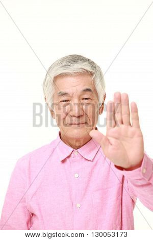 portrait of senior Japanese man making stop gesture on white background