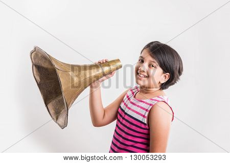 small indian girl shouting / yelling in an vintage brass gramophone speaker, isolated over white background