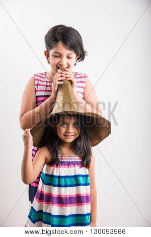 small indian girl wearing gramophone speaker in head and one girl shouting / yelling in an vintage brass gramophone speaker, isolated over white background