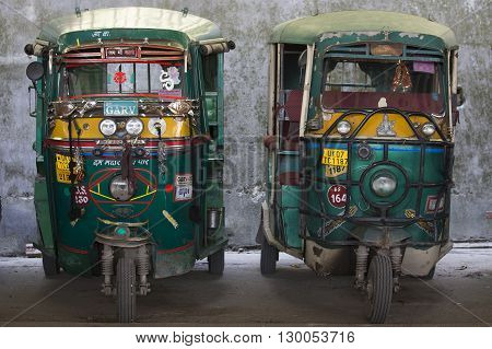 RISHIKESH INDIA - OCTOBER 19 2014 : Auto rickshaw taxis on a road. These iconic taxis have recently been fitted with CNG powered engines in an effort to reduce pollution