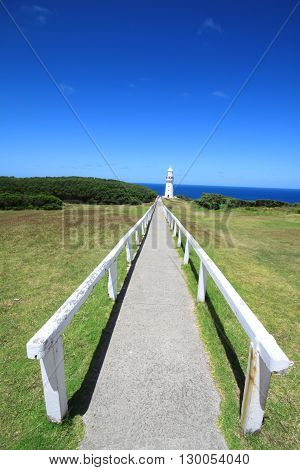 Walk rail heading up to a light house with the sea in the background