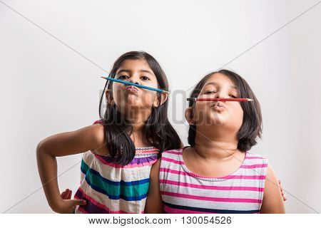 two Naughty little indian girls holding a pencil like a mustache. 2 asian girls holding pencil like mustache, Concept of education. isolated over white background