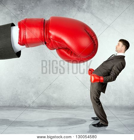 Businessman in boxing gloves against big boxing glove