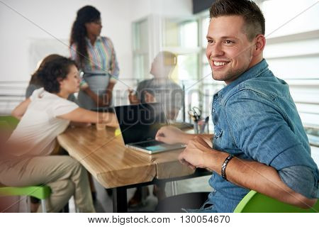 Creative millenial businessman leading his team in a friendly conversation about their next agency project