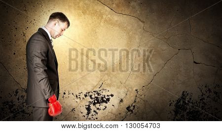 Businessman wearing boxing gloves and looking sad on grey wall background with light