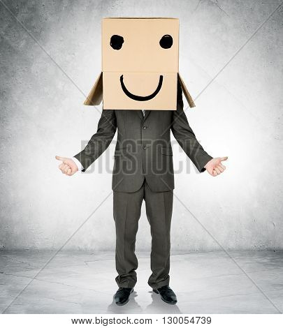 Businessman gesturing with box on head and smiley face