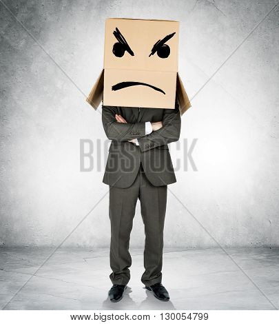 Depressed man with box over head with crossed arms