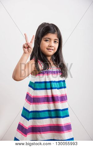 indian small girl counting two, asian small girl showing 2 fingers or two numbers with fingers