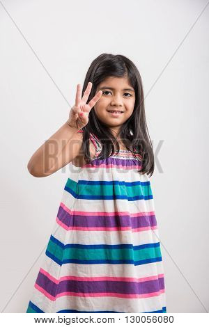 indian small girl counting three, asian small girl showing 3 fingers or three numbers with fingers