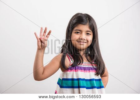 indian small girl counting four, asian small girl showing 4 fingers or four numbers with fingers