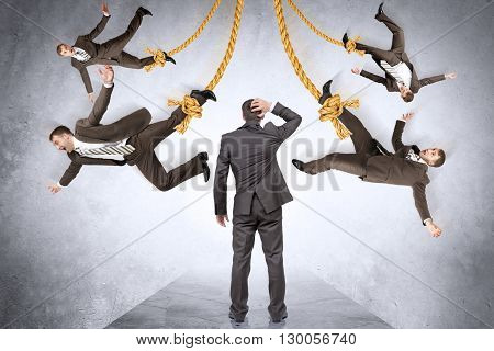 Confused businessman looking on hanging people on rope