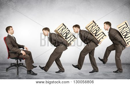Businessmen carry boxes with word tribute to boss