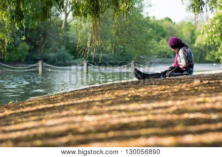 LONDON UK - MAY 16 2016  Lady painting by lake in Regent's Park. An artist in purple beret sketching in tranquil evening sun in one of London's Royal Parks surrounded by willows